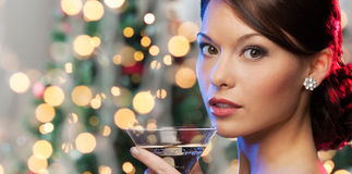 Woman with cocktail over christmas tree lights Royalty Free Stock Photography