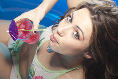 Woman with cocktail in pool Stock Photography
