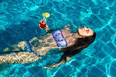 Woman with cocktail in pool Stock Images