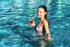 Woman with cocktail in pool Royalty Free Stock Image