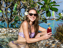Woman with cocktail in pool Royalty Free Stock Images