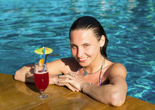 Woman with cocktail in pool Stock Image