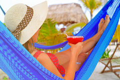 Woman with cocktail relaxed in hammock on the Stock Photo