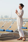 Woman with cocktail standing on cruise liner deck Royalty Free Stock Images