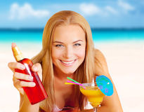 Woman with cocktail and sunblock on the beach Stock Photography