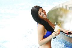 Woman with cocktail in swimming pool Stock Images