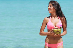 Woman with coconut cocktail on beach. Beautiful smiling young woman in bikini with coconut cocktail on beach Royalty Free Stock Image