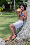 Woman with coconut rests on palm tree. Asian young woman with coconut rests on palm tree Stock Photography