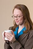 Woman with coffee-01. A young business woman looks down with pleasure at a mug of coffee she is holding Stock Images