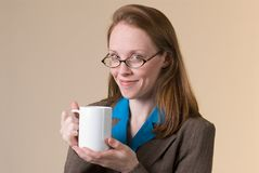 Woman with coffee-04. A young business woman looks up with pleasure while holding a mug of coffee Royalty Free Stock Image
