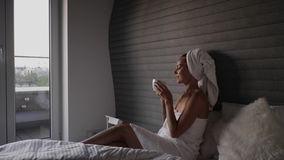Woman with coffee on a bed in a hotel room stock video footage
