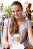 Woman with coffee in cafe. Portrait of charming smiling woman with coffee in outdoor city cafe is looking straight into camera Stock Photo