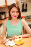 Woman with coffee and cake in kitchen. Gluttony. Royalty Free Stock Photography