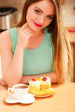 Woman with coffee and cake in kitchen. Gluttony. Stock Photo