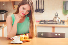 Woman with coffee and cake in kitchen. Gluttony. Stock Image