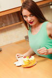Woman with coffee and cake in kitchen. Gluttony. Stock Images