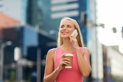 Woman with coffee calling on smartphone in city Stock Images