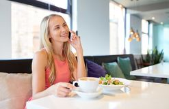 Woman with coffee calling smartphone at restaurant Stock Photography