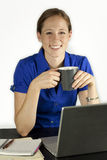 Woman With a Coffee Cup. A pretty businesswoman enjoying a cofee break at her desk Stock Photos