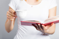 Woman with coffee cup and book in her hands Stock Photo