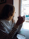 Woman with coffee cup in hands sitting near the window. Cafe Stock Photos