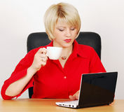 Woman with coffee-cup and laptop Royalty Free Stock Photos