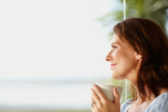 Woman with a coffee cup looking at copy space Stock Photo