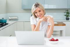 Woman with coffee cup looking at laptop in kitchen Royalty Free Stock Photos