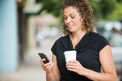 Woman With Coffee Cup Messaging Through Smartphone. Beautiful woman with disposable coffee cup text messaging through smartphone outdoors Royalty Free Stock Images