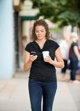 Woman With Coffee Cup Using Smartphone On Pavement Royalty Free Stock Photo