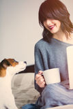 Woman with of coffee, dog and notebook. Portrait of a young caucasian woman with of coffee, dog and notebook at home Stock Photography