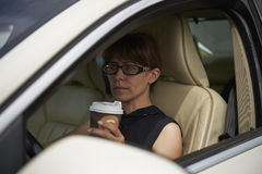 Woman with a coffee while driving car royalty free stock photo