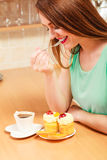 Woman with coffee eating cream cake. Gluttony. Stock Photography