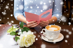 Woman with coffee and flower reading greeting card Stock Photos