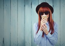 Woman with coffee and hat against blue wood panel. Digital composite of Woman with coffee and hat against blue wood panel royalty free stock photos