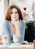Woman at the coffee house and man with rose behind her Royalty Free Stock Images