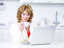 Woman with coffee and laptop in the kitchen Stock Photo