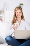 Woman With Coffee And Laptop On Sofa Stock Images