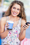 Woman with coffee and mobile phone Royalty Free Stock Photo