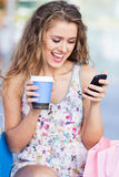 Woman with coffee and mobile phone Stock Images