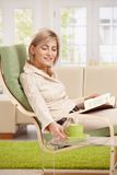 Woman with coffee mug and book at home Stock Images
