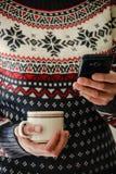 Woman with coffee mug reading the news on the phone stock image