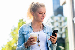 Woman with coffee and phone in city Stock Photos