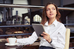 Woman with coffee reading news Stock Photo