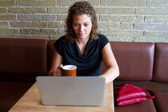 Woman at coffee shop with computer Royalty Free Stock Image