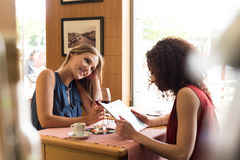 Woman at coffee shop table. Pretty women talking and having fun inside coffee shop Stock Photography