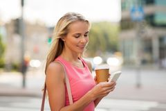 Woman with coffee and smartphone in city Royalty Free Stock Photos