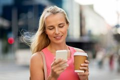 Woman with coffee and smartphone in city Stock Photos