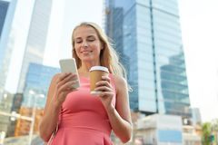 Woman with coffee and smartphone in city Stock Photography