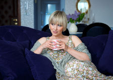 Woman with coffee on sofa Royalty Free Stock Photo